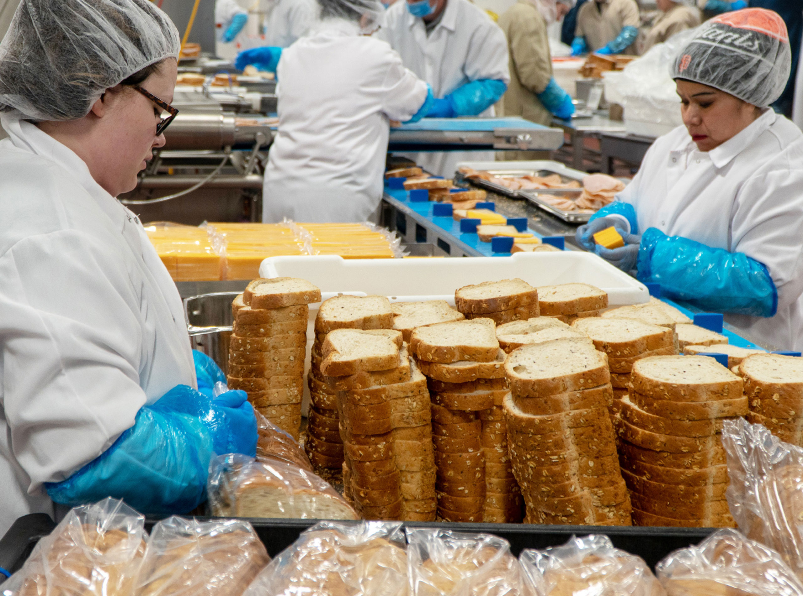 Workers assembling sandwiches
