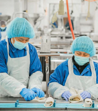 Women working in hairnets and masks